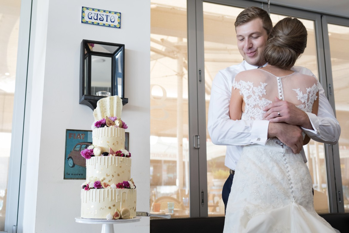 beautiful wedding cake white with drips gold foil pink flowers fruit macaroons by petite crumb bride and groom cake cut