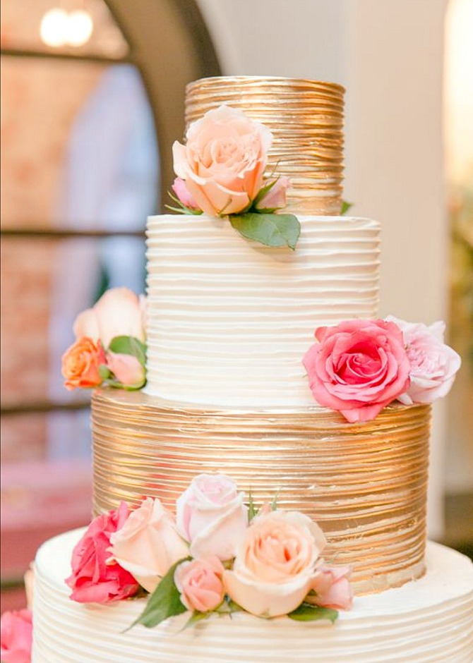 gold and ivory white buttercream four tier wedding cake with bright fresh rose flowers | Semi Naked Drip Wedding Cakes featured by popular US lifestyle blogger, Style Elixir